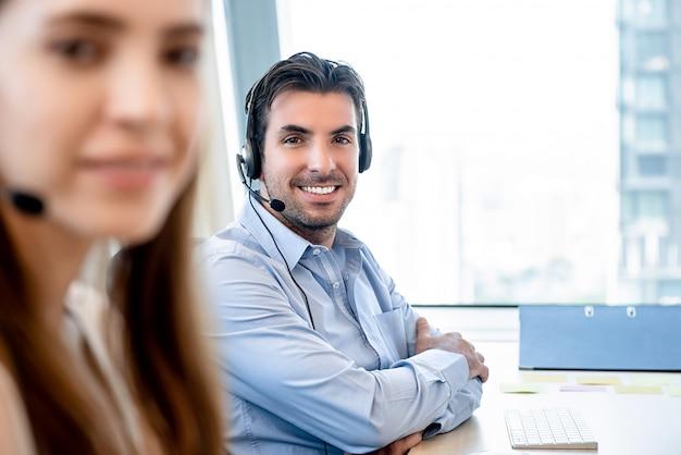 Glimlachende vriendschappelijke spaanse mens die in call centre werkt