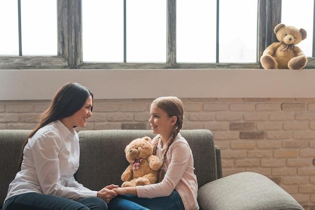 Glimlachende vriendschappelijke vrouwelijke psycholoog die met meisjeszitting op bank spreekt