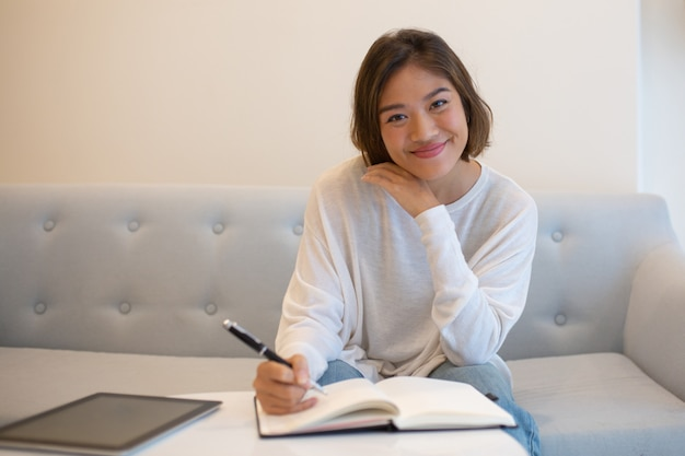 Glimlachende vrij aziatische vrouw die thuis bestudeert