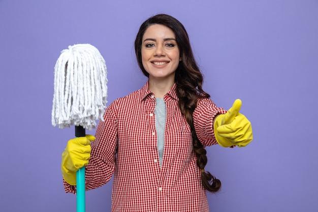 Glimlachende vrij blanke schonere vrouw met rubberen handschoenen die dweil vasthouden en omhoog duimen