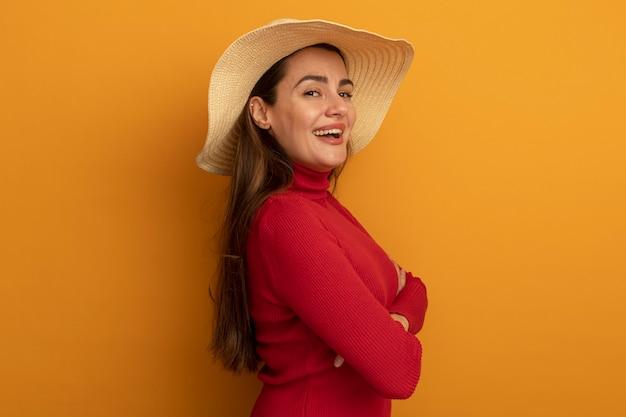 Glimlachende vrij blanke vrouw met strandhoed staat zijwaarts met gekruiste armen op oranje