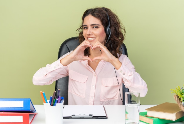 Glimlachende vrij blanke vrouwelijke callcenter-operator op een koptelefoon die aan het bureau zit met kantoorhulpmiddelen die een hartteken gebaar maken