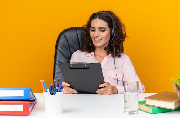 Glimlachende vrij blanke vrouwelijke callcenter-operator op koptelefoon zittend aan een bureau met kantoorhulpmiddelen die klembord vasthouden en bekijken