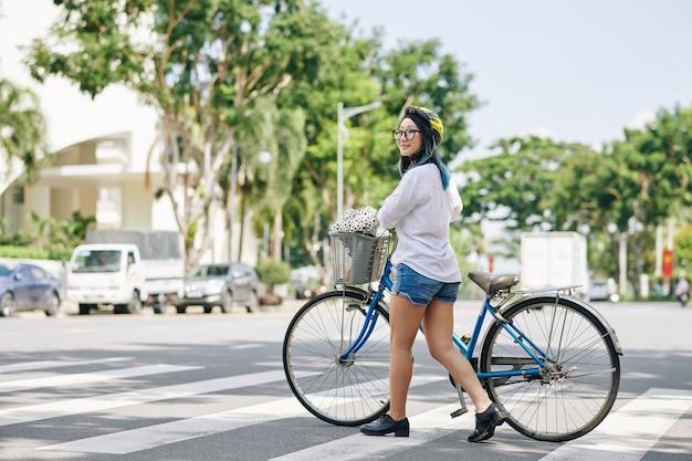 Glimlachende vrij chinese vrouw die in helm naast haar fiets loopt bij het oversteken van de weg