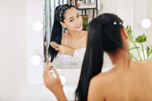 Glimlachende vrij jonge aziatische vrouw die haar borstelt