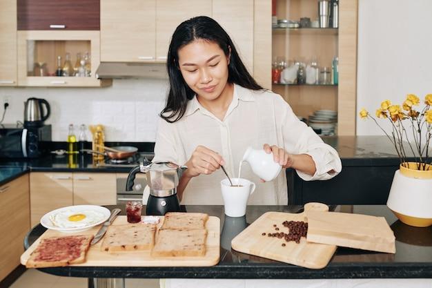 Glimlachende vrij jonge aziatische vrouw die melk in haar ochtendkoffie toevoegt bij het eten van ontbijt