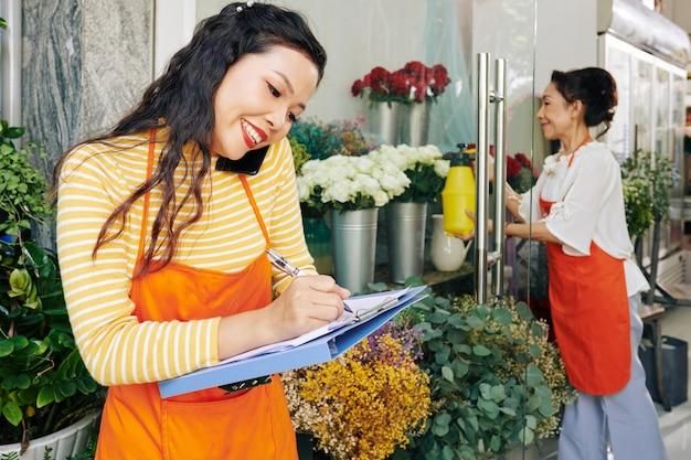Glimlachende vrij jonge bloemist die op telefoon met klant spreekt en notities in document maakt