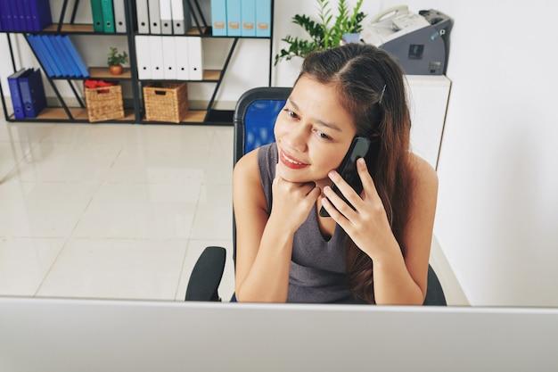 Glimlachende vrij jonge gemengde ras onderneemster die document op computerscherm leest en op telefoon spreekt met collega of cliënt