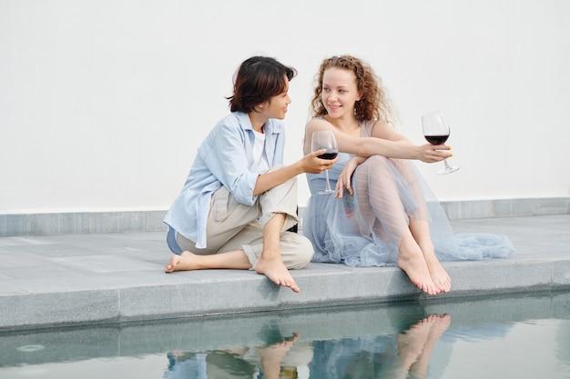 Glimlachende vrij jonge vrouwen die bij zwembad zitten, wijn drinken en ideeën bespreken