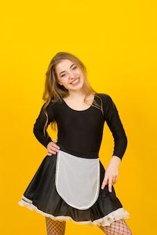 Glimlachende vrij jonge vrouwenhuisvrouw in vrijetijdskleding, die huishoudelijk werk doet dat op geel studioportret wordt geïsoleerd als achtergrond. huishouding concept. bespreek kopie ruimte.