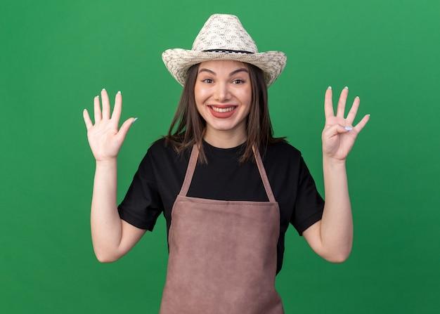 Glimlachende vrij kaukasische vrouwelijke tuinman die het tuinieren hoed draagt die negen met vingers op groen gebaart
