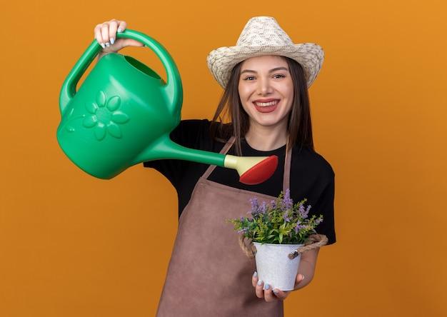Glimlachende vrij kaukasische vrouwelijke tuinman die tuinieren hoed draagt, beweert bloemen in bloempot met gieter te bewateren die op oranje muur met exemplaarruimte wordt geïsoleerd