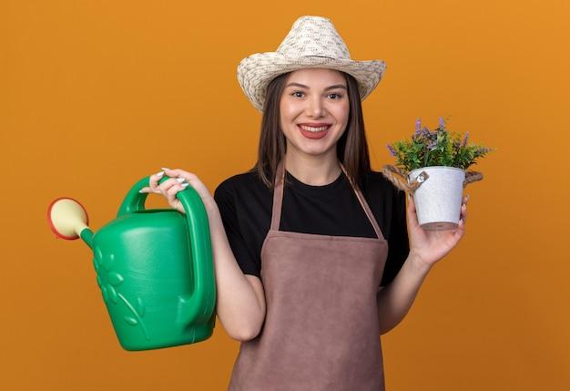 Glimlachende vrij kaukasische vrouwelijke tuinman die tuinieren hoed draagt die gieter en bloempot houdt die op oranje muur met exemplaarruimte wordt geïsoleerd