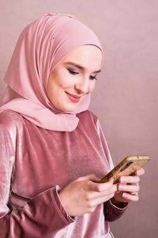 Glimlachende vrij moslimvrouw die mobiele telefoon met behulp van