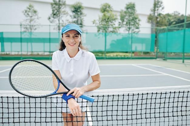 Glimlachende vrij vrouwelijke tennisspeelster