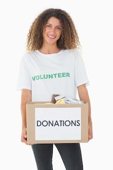 Glimlachende vrijwilliger die een doos van schenkingen houdt