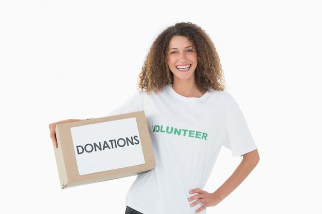 Glimlachende vrijwilliger die een doos van schenkingen met hand op heup houdt