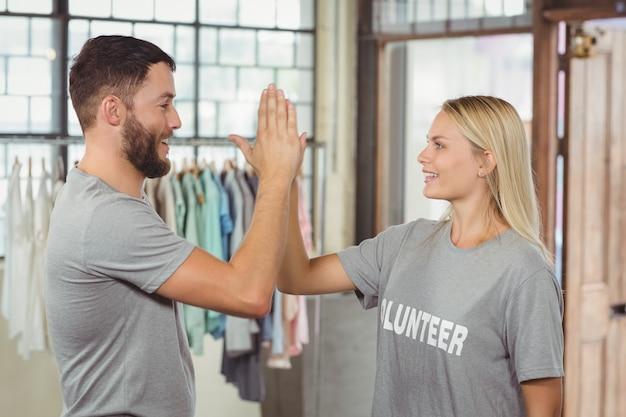 Glimlachende vrijwilliger die hoge vijf doen terwijl het werken op kantoor