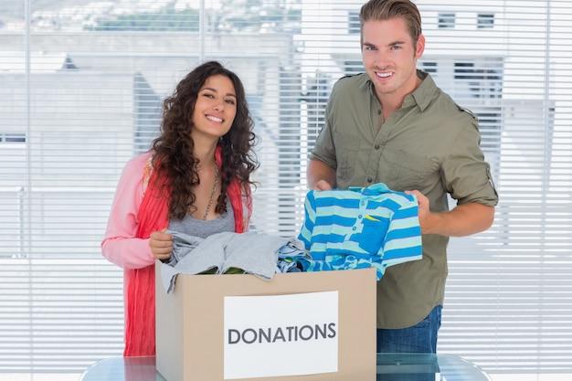 Glimlachende vrijwilligers die kleren van schenkingendoos weghalen