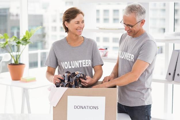 Glimlachende vrijwilligers die schenkingsdoos sorteren