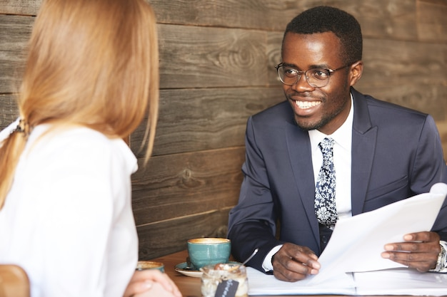 Glimlachende vrolijke afrikaanse amerikaanse ondernemer die glazen en formeel kostuum draagt