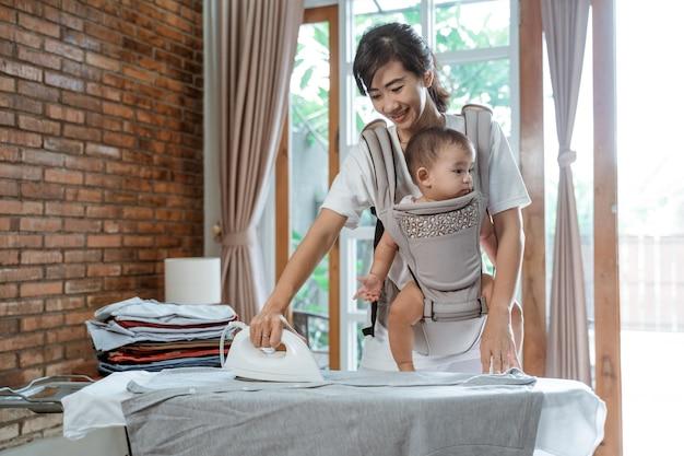 Glimlachende vrolijke aziatische vrouw die wasgoed strijken terwijl ze haar babymeisje vasthoudt