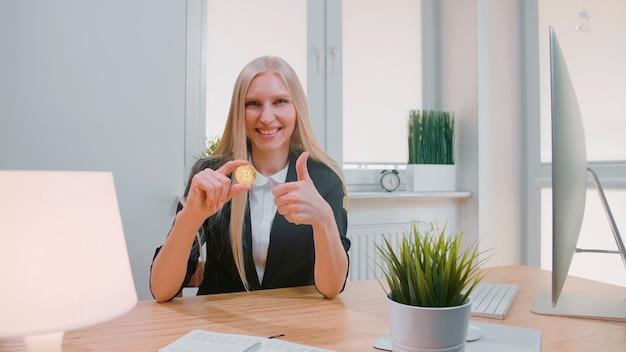 Glimlachende vrolijke blonde vrouw in kantoorpak zit op de werkplek met computer en toont bitcoin i...