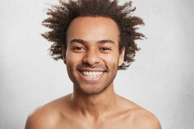 Glimlachende vrolijke jonge afro-amerikaanse man positieve emoties uitdrukt zoals goed humeur na wandeling