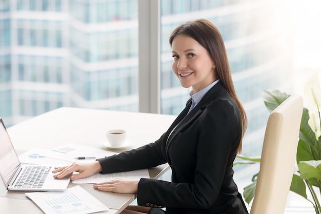 Glimlachende vrolijke jonge onderneemster die bij bureau met laptop werkt