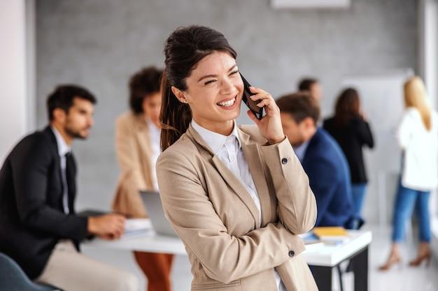 Glimlachende vrolijke jonge onderneemster die zich in directiekamer bevindt en aan de telefoon spreekt.