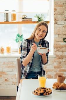 Glimlachende vrolijke jonge vrouw die in de keuken zit met een kom ontbijtgranen