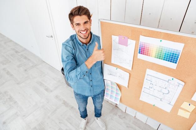 Glimlachende vrolijke man die op het taakbord staat en een duim omhoog gebaar op kantoor laat zien