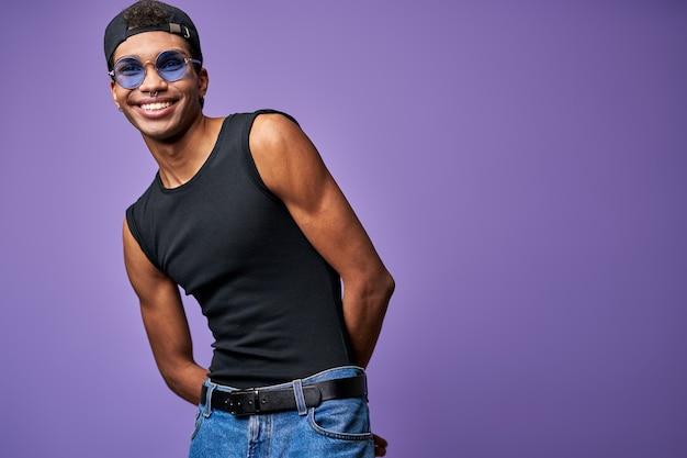 Glimlachende vrolijke man in een blauwe bril portret gelukkige jonge transgender man in casual pose