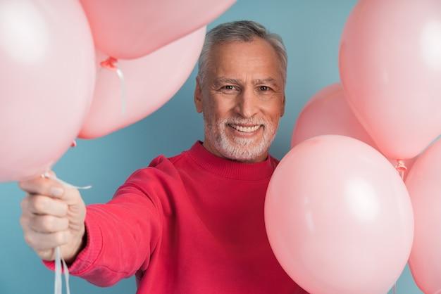 Glimlachende, vrolijke man met ballonnen poseren