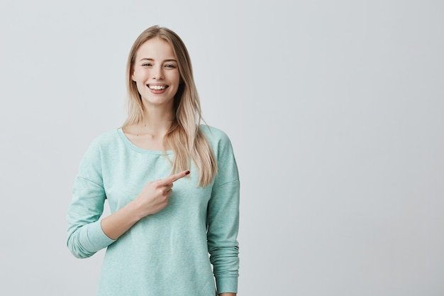 Glimlachende vrolijke positieve europese vrouw die lichtblauw overhemd draagt dat haar wijsvinger opzij op exemplaarruimte richt