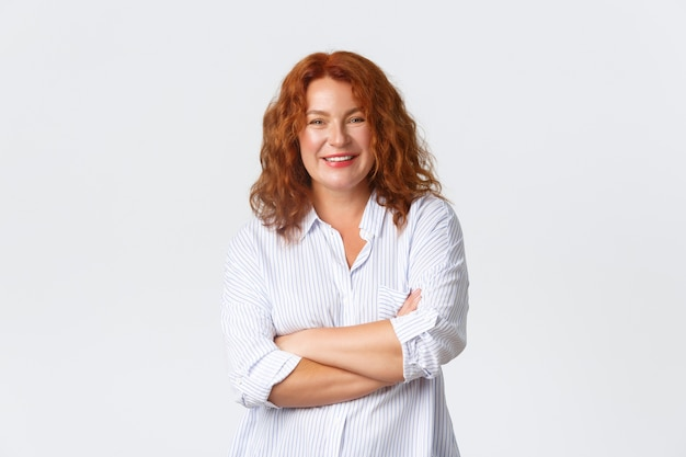 Glimlachende vrolijke roodharige vrouw van middelbare leeftijd, die zich professioneel voelt, dwars op de borst. volwassen vrouwtje dat een eigen bedrijf begint, staande witte muur.