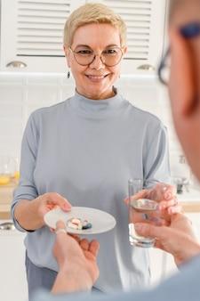 Glimlachende, vrolijke, volwassen vrouw die een glas water vasthoudt en voedingssupplement vitaminepillen neemt