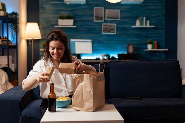 Glimlachende vrolijke vrouw die fastfood uitpakt, thuisbezorgd zittend op de bank