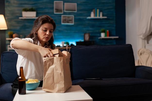 Glimlachende vrolijke vrouw die fastfoodmaaltijden uitpakt die op de bank zitten tijdens thuisbezorgd junkfood