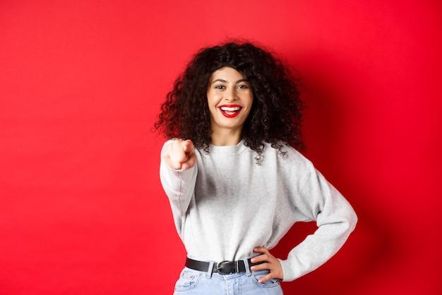 Glimlachende vrolijke vrouw met krullend kapsel die met de vingers naar de camera wijst en je uitnodigt om iemand te kiezen...