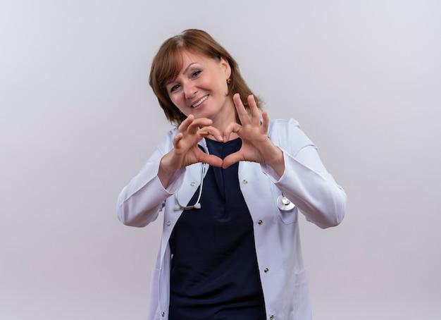 Glimlachende vrouw arts die op middelbare leeftijd medische mantel en stethoscoop draagt die hartteken op geïsoleerde witte muur met exemplaarruimte doen