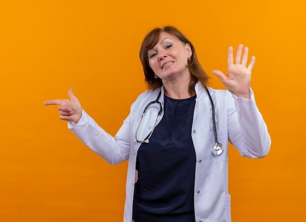 Glimlachende vrouw arts die op middelbare leeftijd medische mantel en stethoscoop draagt die naar linkerkant richt en vijf op geïsoleerde oranje muur toont