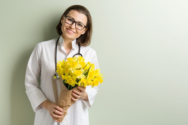 Glimlachende vrouw arts met boeket van bloemen.
