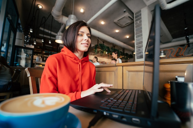 Glimlachende vrouw bij de bar die een koffie heeft en laptop met behulp van