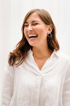 Glimlachende vrouw bij het witte gordijn