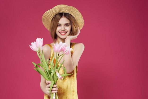 Glimlachende vrouw boeket bloemen hoed glamour cosmetica close-up