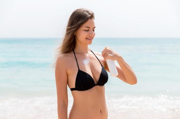 Glimlachende vrouw brengt zonnebrandcrème van de spray op haar lichaam aan op de achtergrond van de zee.