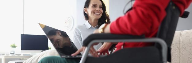 Glimlachende vrouw communiceert met vrouw in rolstoel met laptop