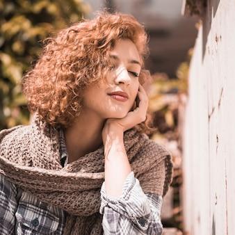Glimlachende vrouw dichtbij het gezicht van de muurholding