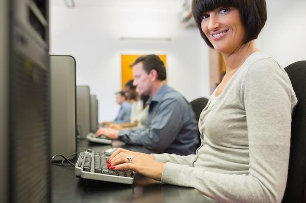 Glimlachende vrouw die aan de computer werkt